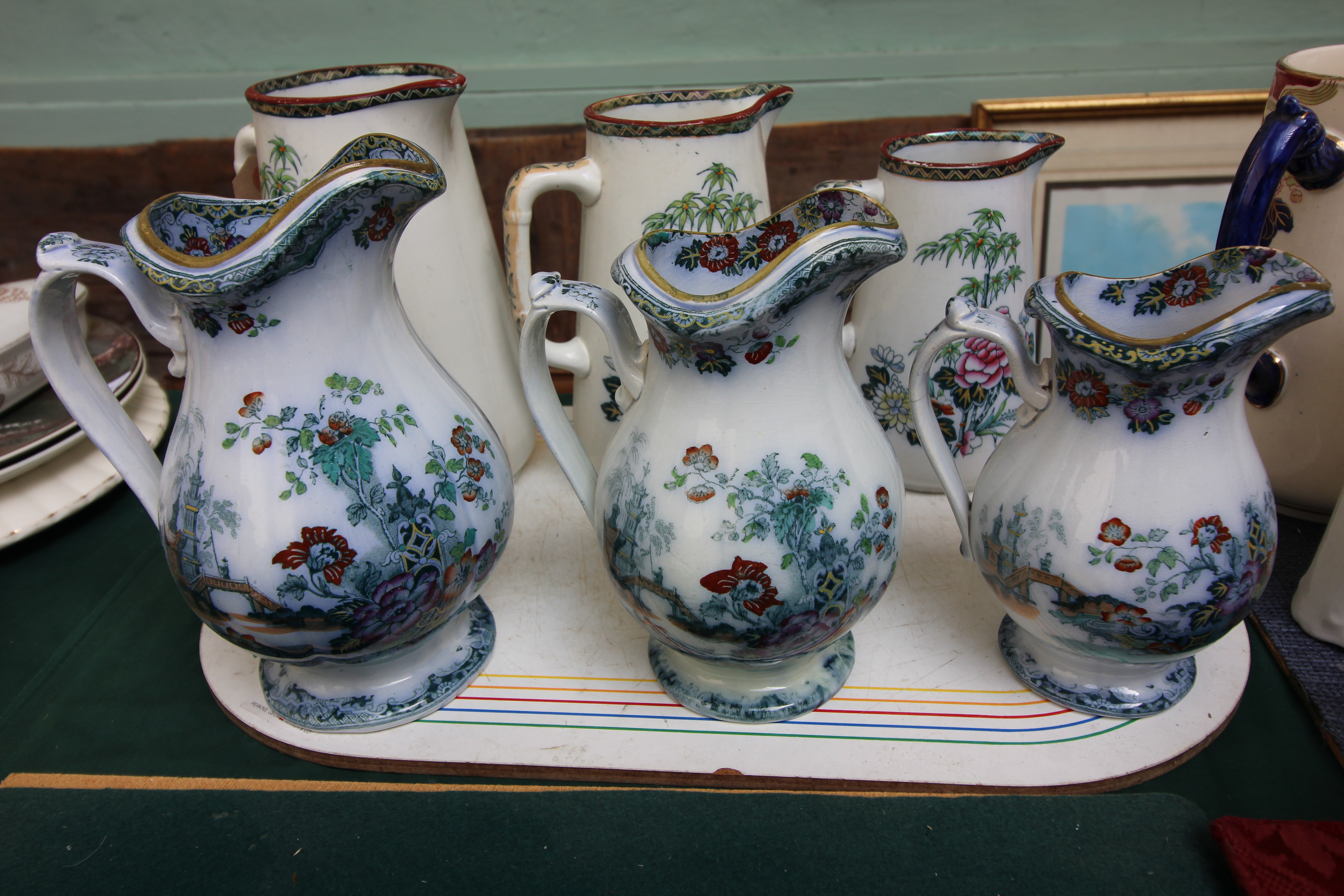 3 Decorative swan china graduated jugs and a further set of three graduated oriental patterned