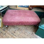 Large rectangular footstool on brass casters the padded top upholstered in patterned maroon floral