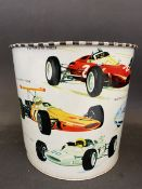 """A waste paper bin decorated with Formula 1 race cars from the 1960s, 7"""" high."""
