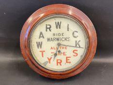A Warwick Tyres circular wall clock.