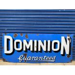 """A Dominion Guaranteed rectangular enamel sign by Stocal, 72 x 30""""."""
