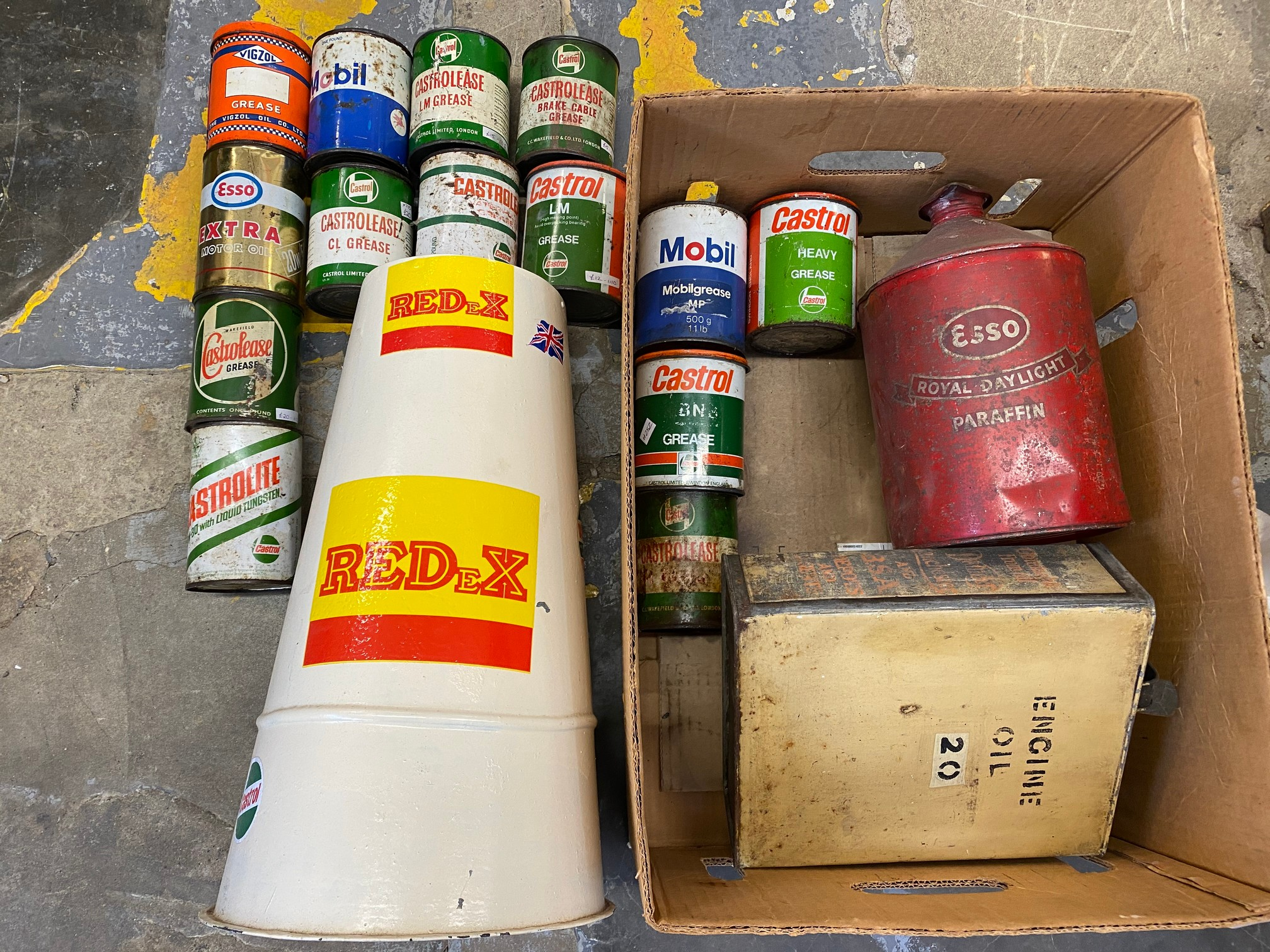 A box of mostly grease tins plus other cans including Esso.