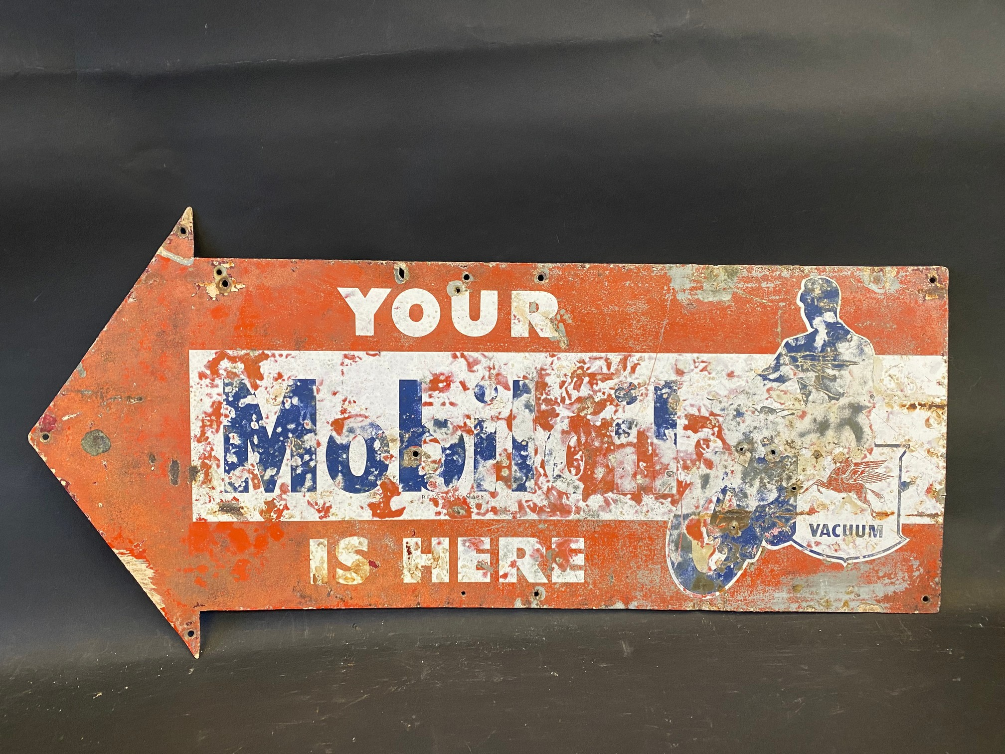 A Mobiloil is here directional arrow tin advertising sign with a faded image of a motorcycle, 24 x 9