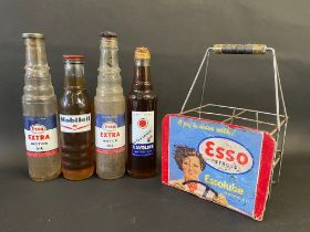 Four pint oil bottles, comprising two Esso Extra, one Mobiloil and a Havoline, in a home made four