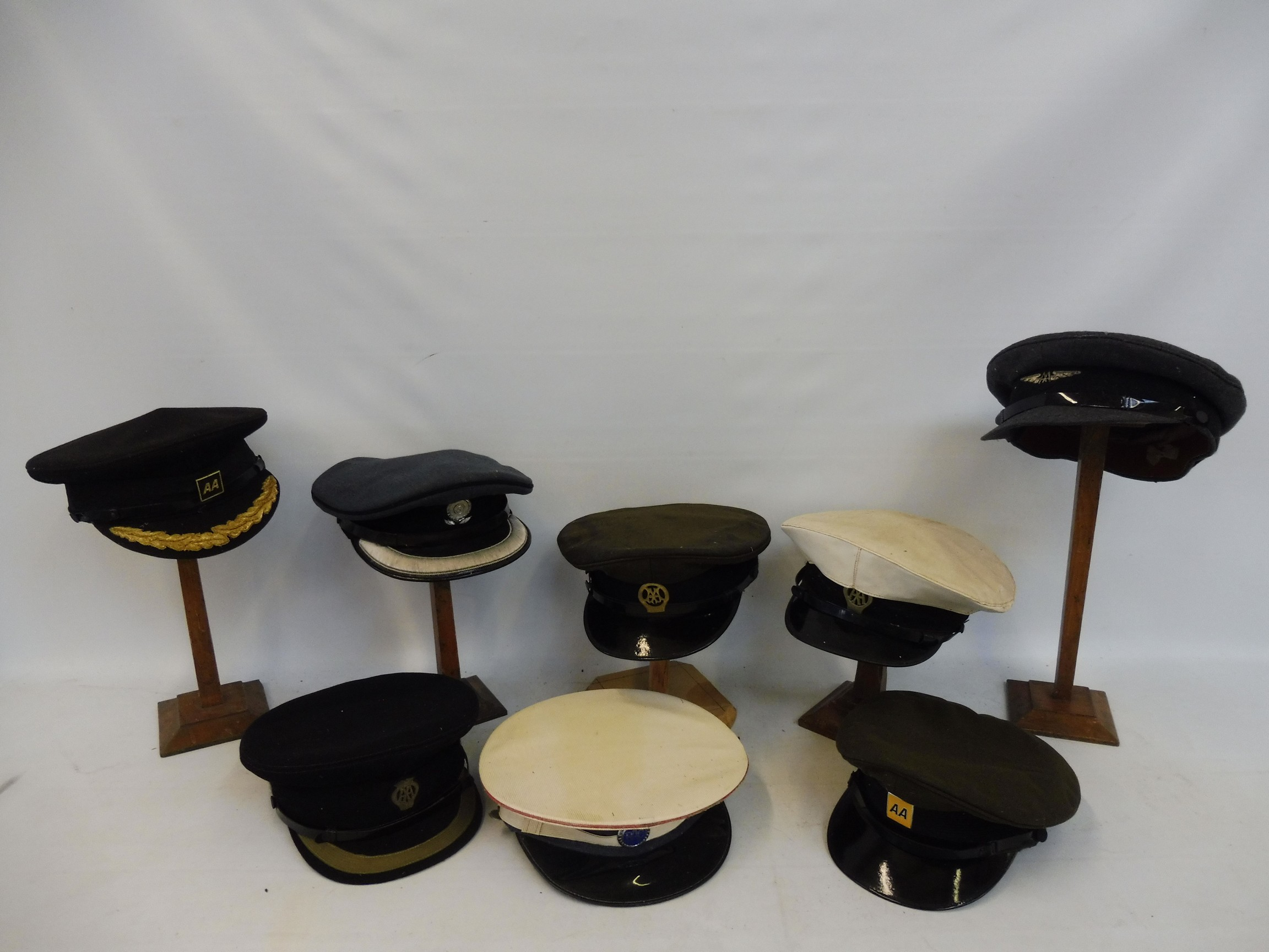 Eight original RAC and AA caps, all with badges attached.