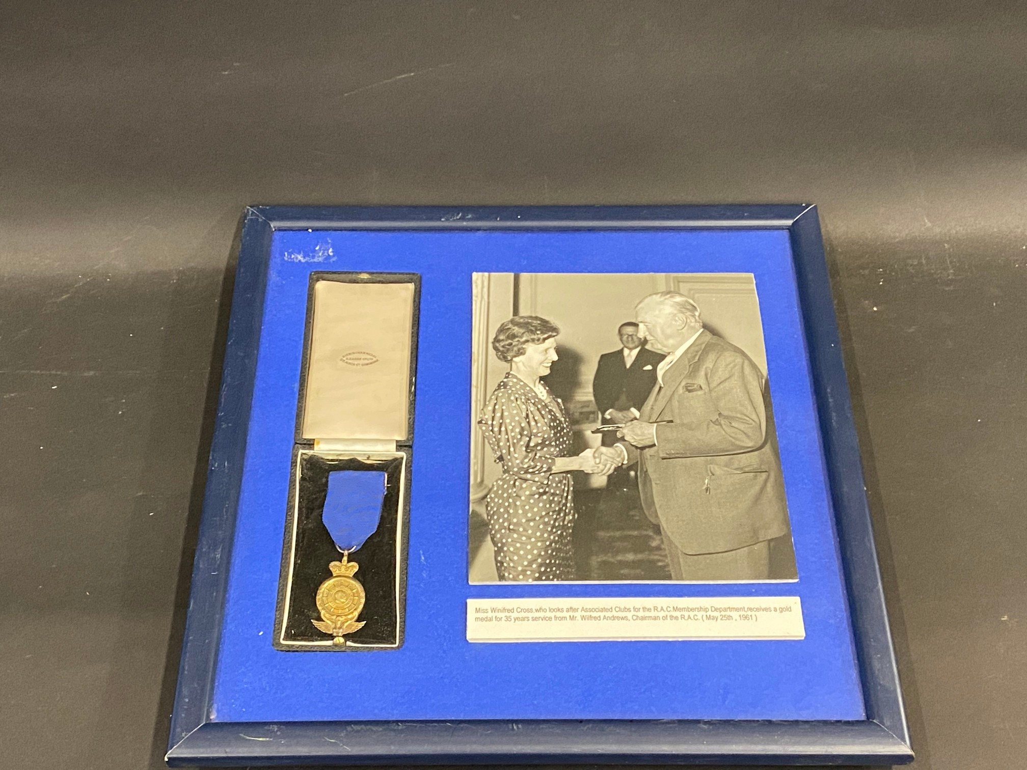 A framed and glazed RAC medal for 35 years service presented to Miss Winifred Cross, who looked