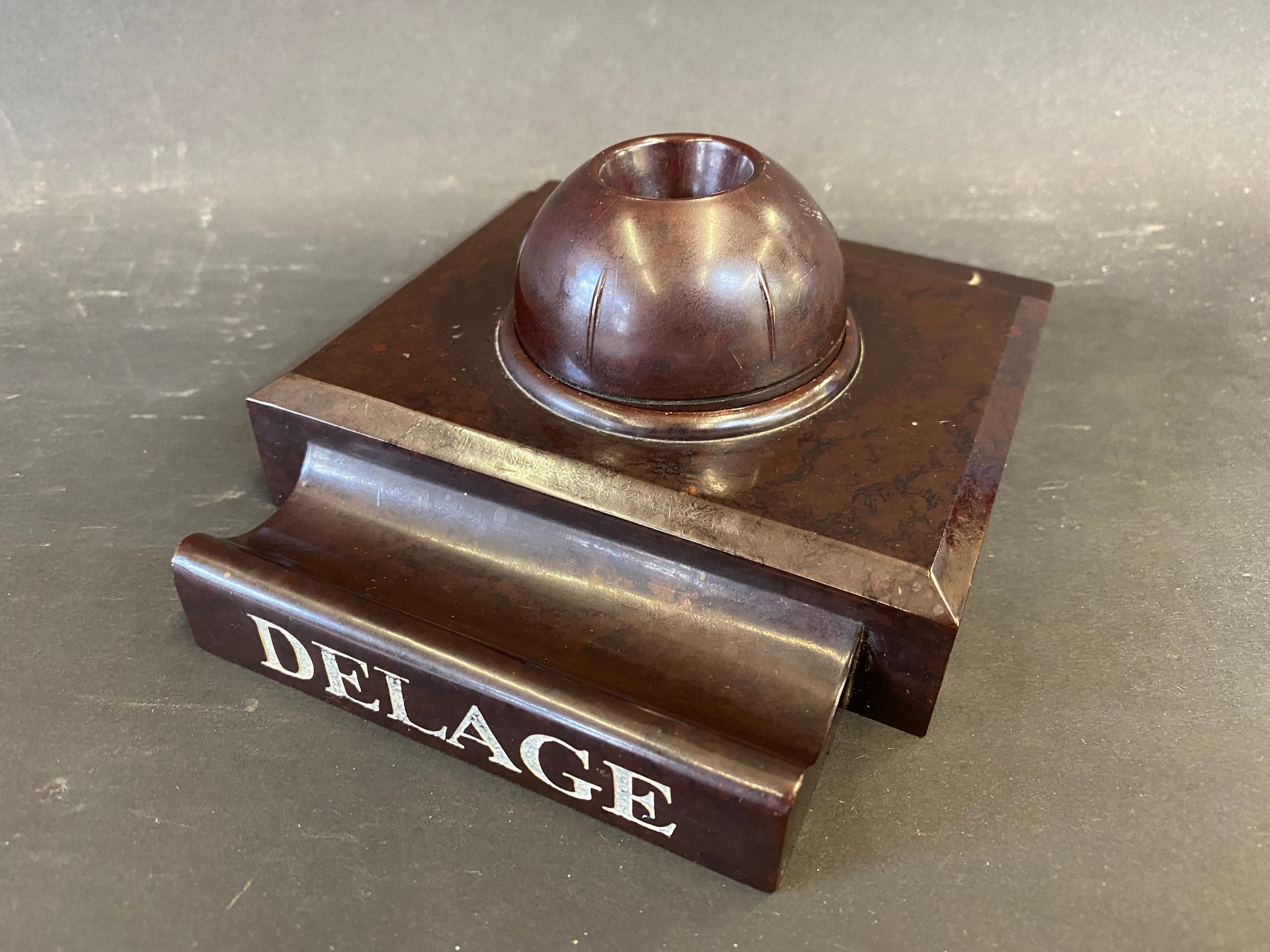 A Delage bakelite style pen holder and inkwell, possibly a salesman's desk piece in a dealership.