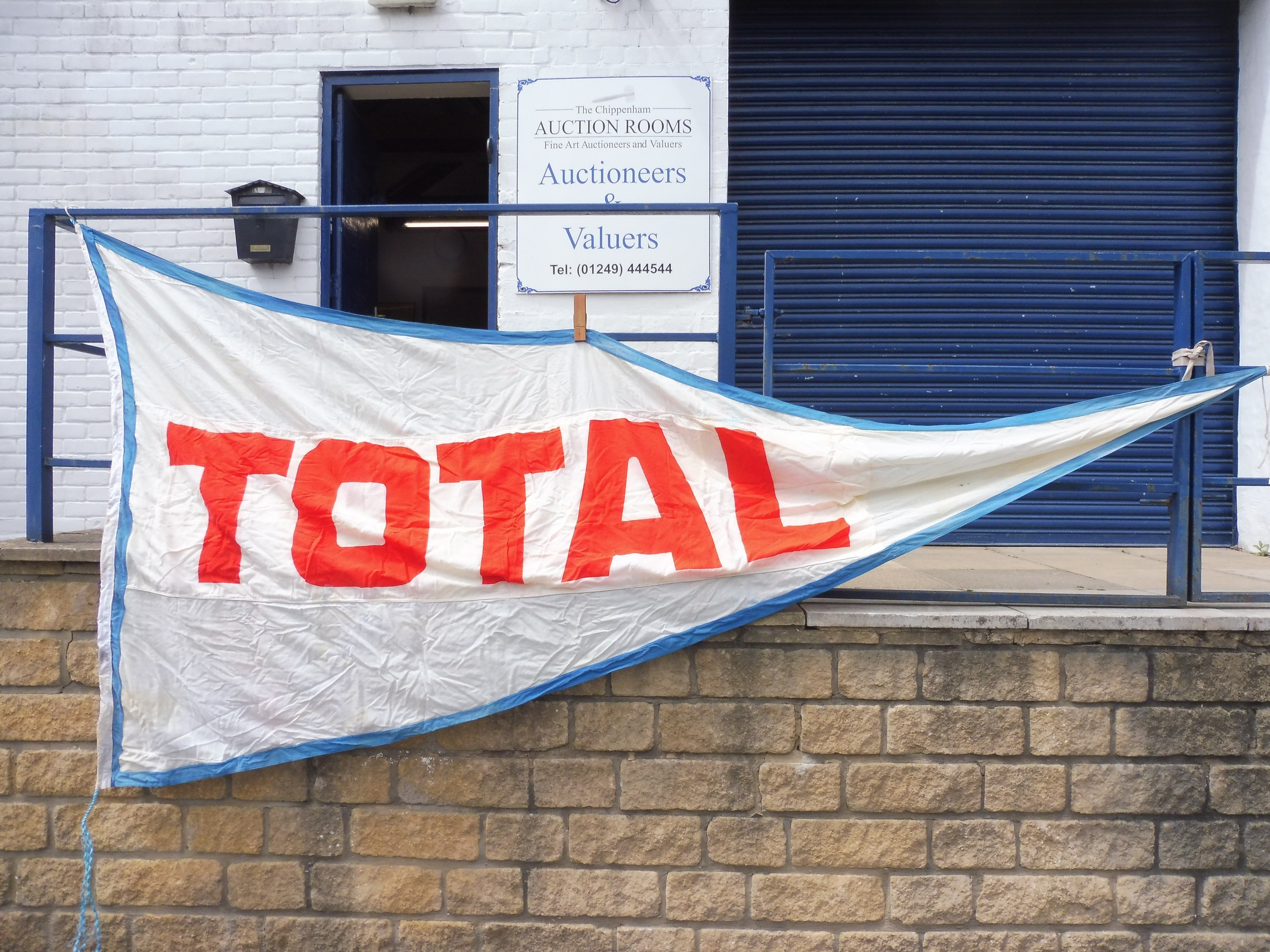 """A large garage forecourt pennant flag advertising TOTAL by Piggotts 11' 11"""" x 68""""."""