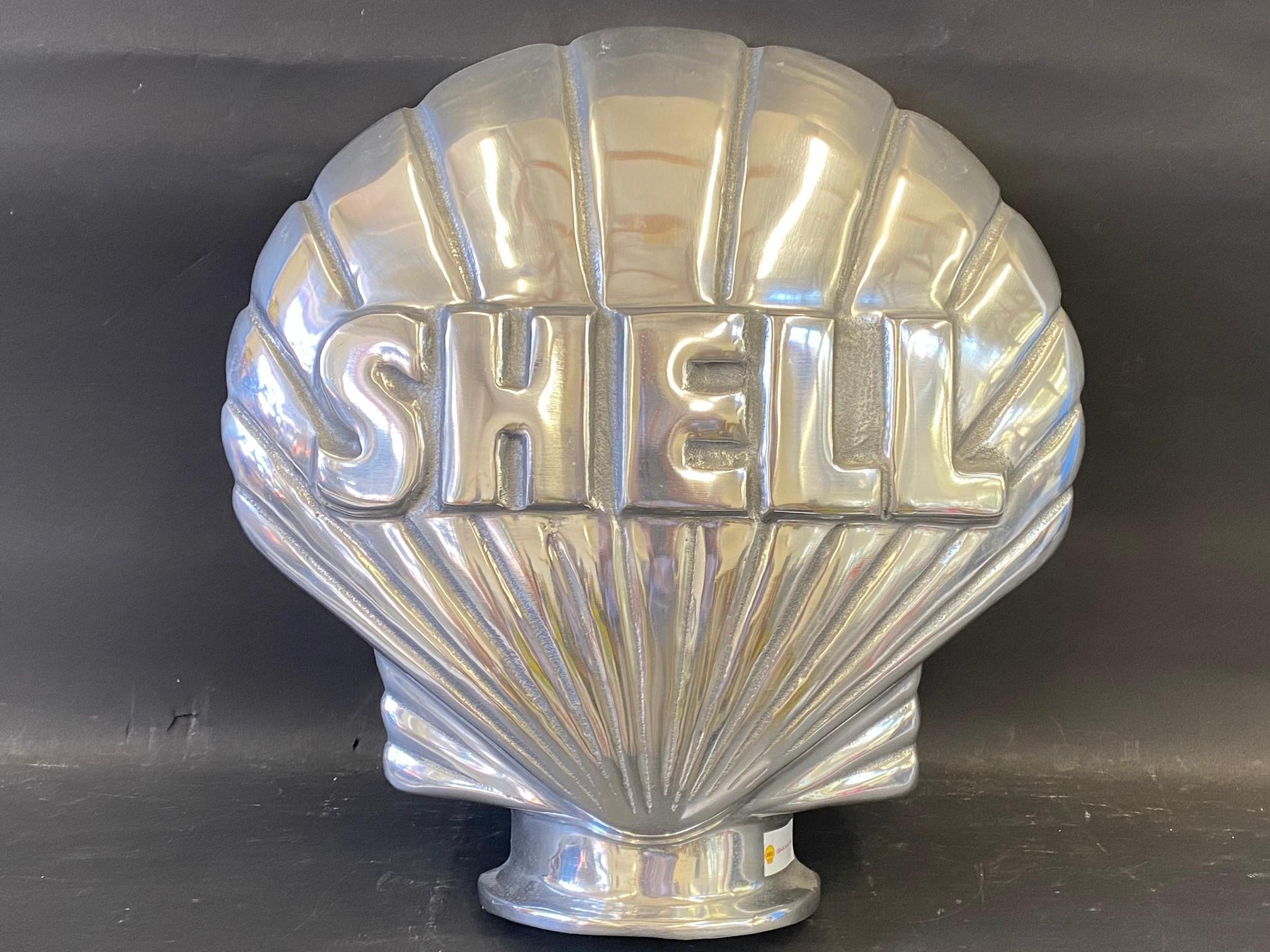A contemporary polished aluminium clam Shell sign, 16 1/2 x 16 1/2.
