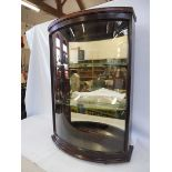 """A bow glass fronted rear opening display cabinet with two glass shelves, 24 3/4"""" w x 35 1/2"""" h x"""