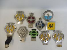 A group of car badges including an AA Commercial badge no. V191021, a parachute corps badge by Gaunt