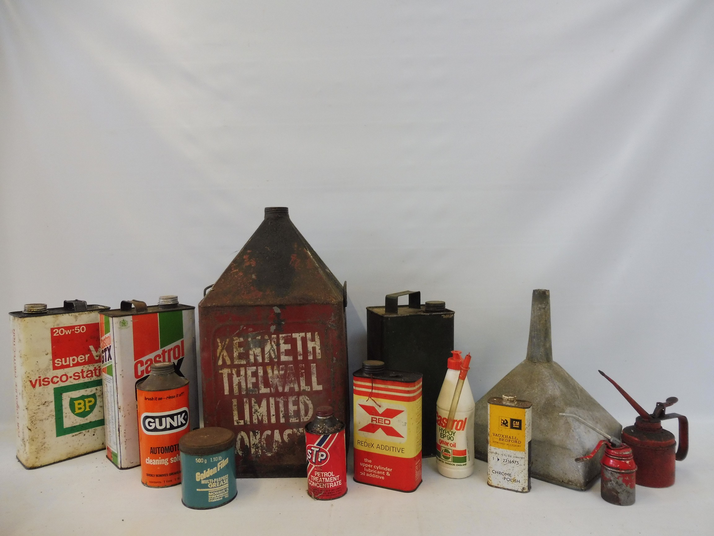 Two crates of assorted oil cans, a funnel etc.