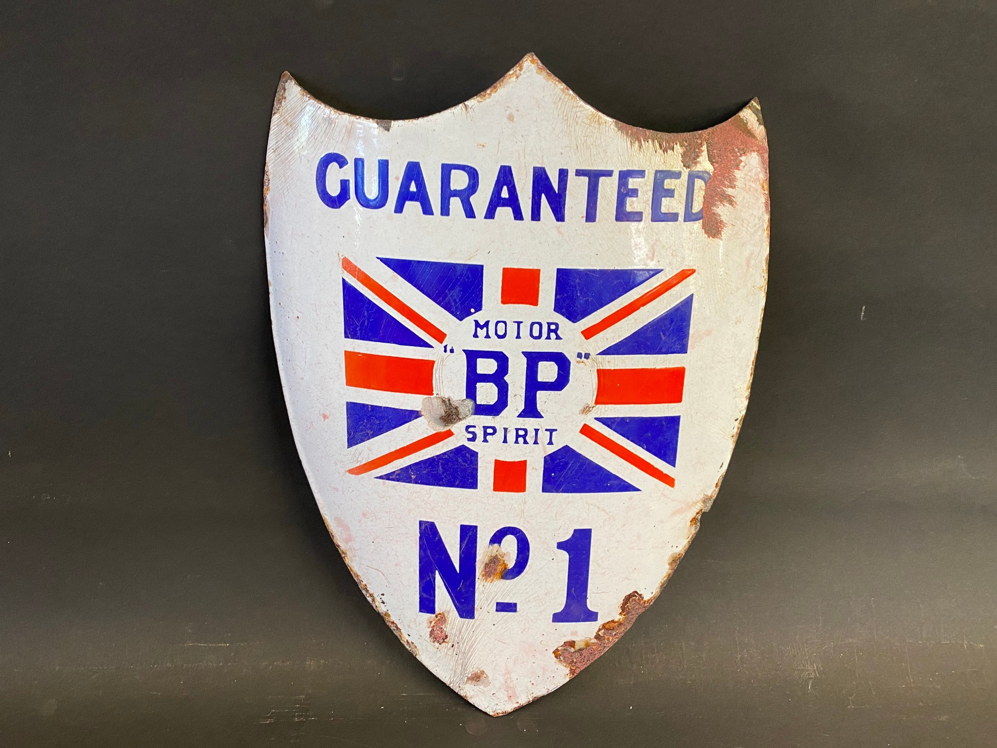 A BP Motor Spirit 'Guaranteed No. 1' shield shaped curved enamel sign with central union jack, 9 x