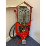 A Watts, Fincham & Co. wall mounted two gallon petrol can, restored in Shell colours with hose and