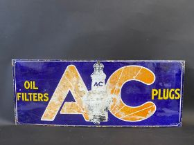 """An AC Oil Filters and Plugs rectangular enamel sign with central plug image, 30 x 12""""."""