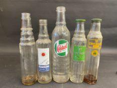 A Wakefield Castrol quart glass oil bottle and four pint oil bottles.