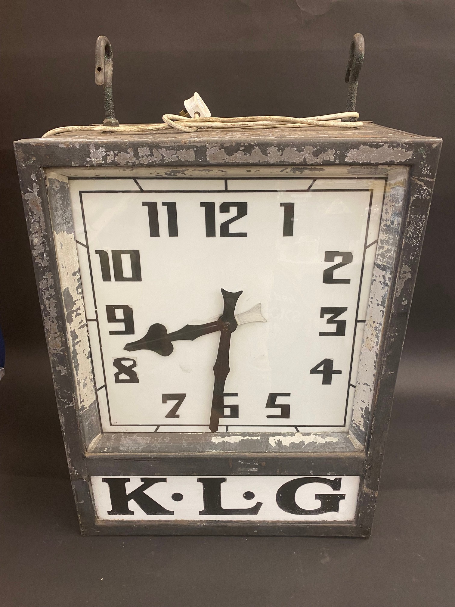 A K.L.G. garage forecourt double sided hanging clock of unusual and attractive form, in very