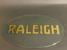 """A Raleigh oval glass garage showrrom bevel edged glass hanging sign, 13 3/4 x 9 1/2""""."""