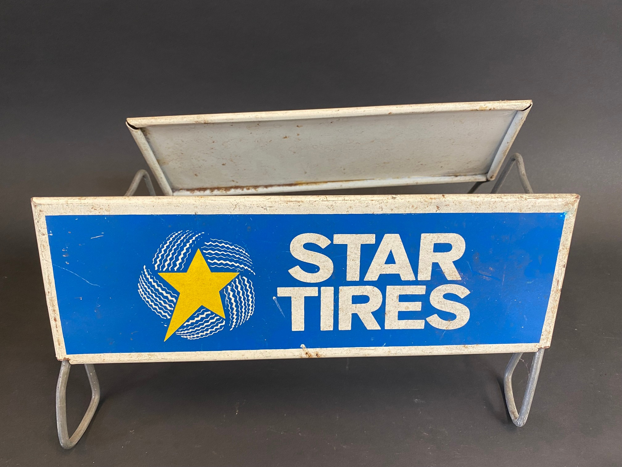 A Star Tires tyre display stand with advertising sign to both sides.