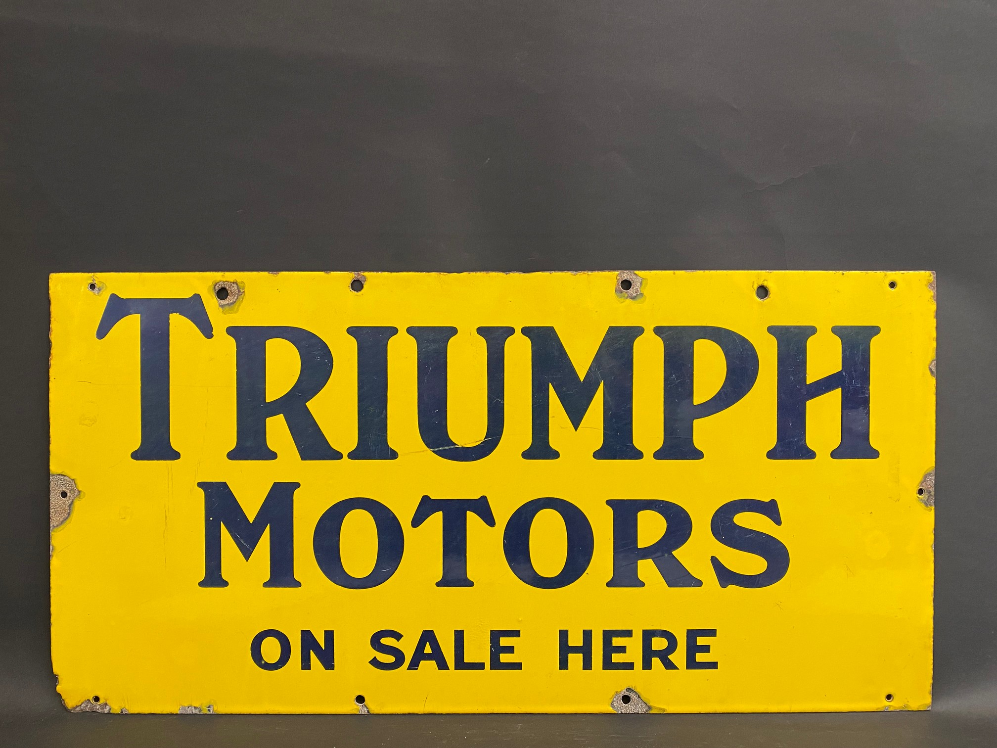 """A Triumph Motors on sale here rectangular enamel sign in excellent condition, 30 x 15""""."""