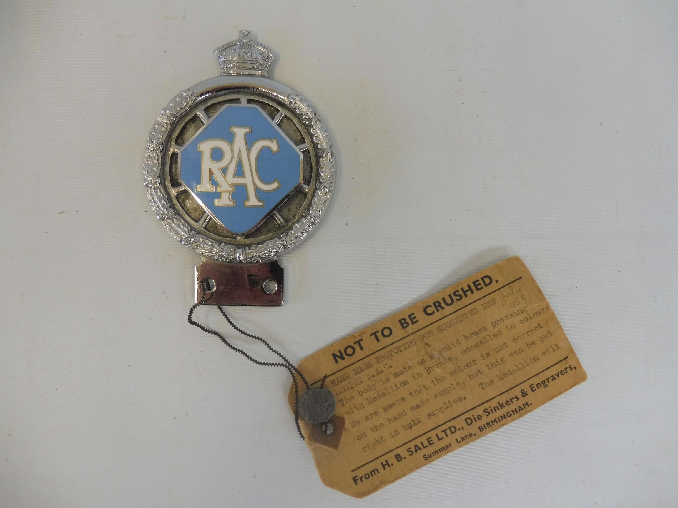 An RAC 1953 prototype car badge, with large lozenge enamel centre, still retaining a cardboard tag