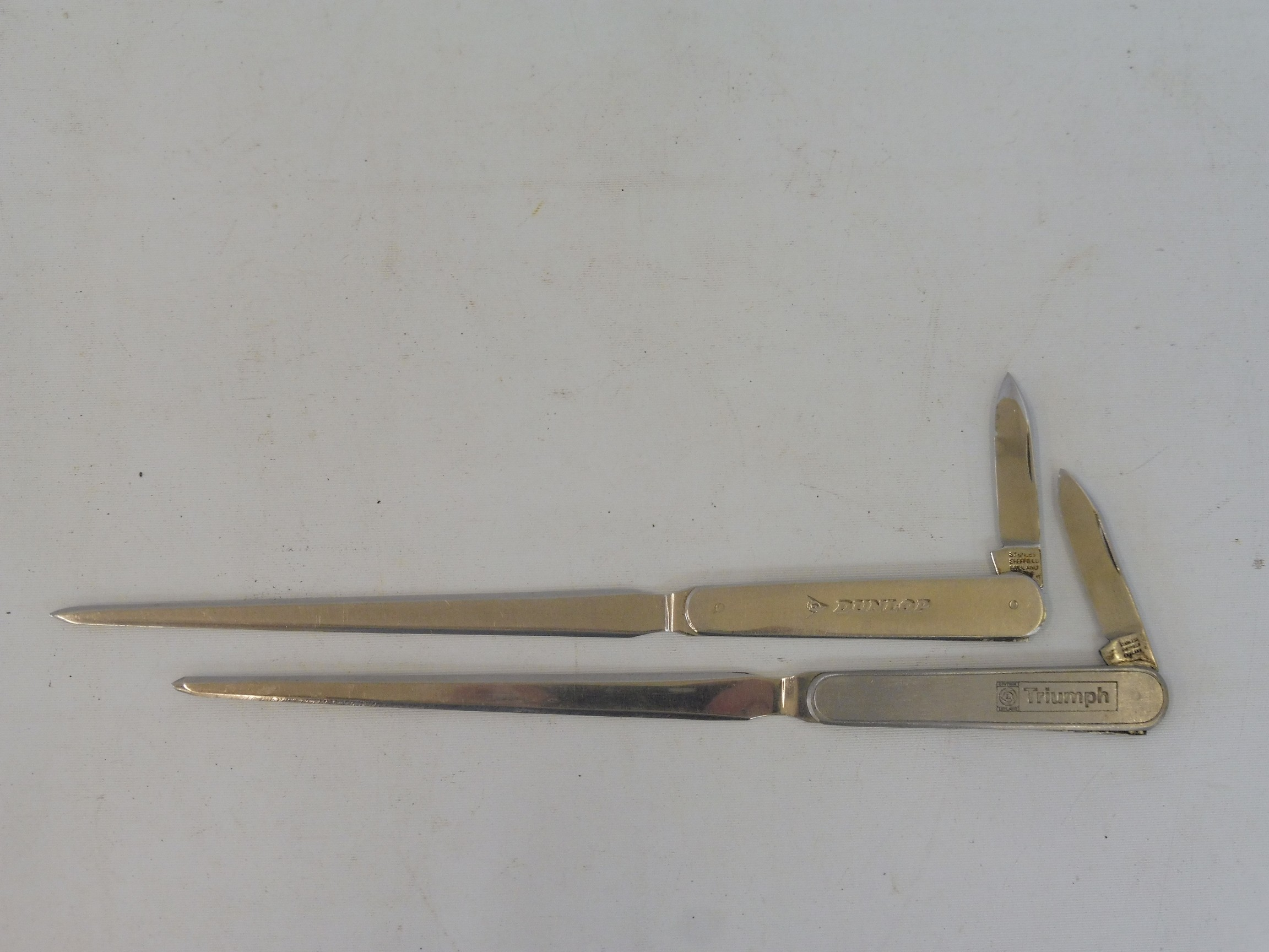 Two letter openers, one advertising Dunlop, the other Triumph (British Leyland).