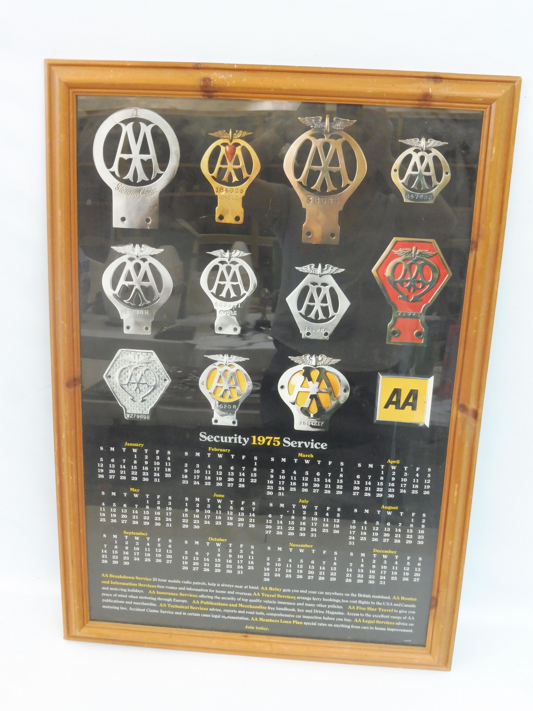 A framed and glazed AA related calendar poster showing the evolution of the AA badge, 1975.