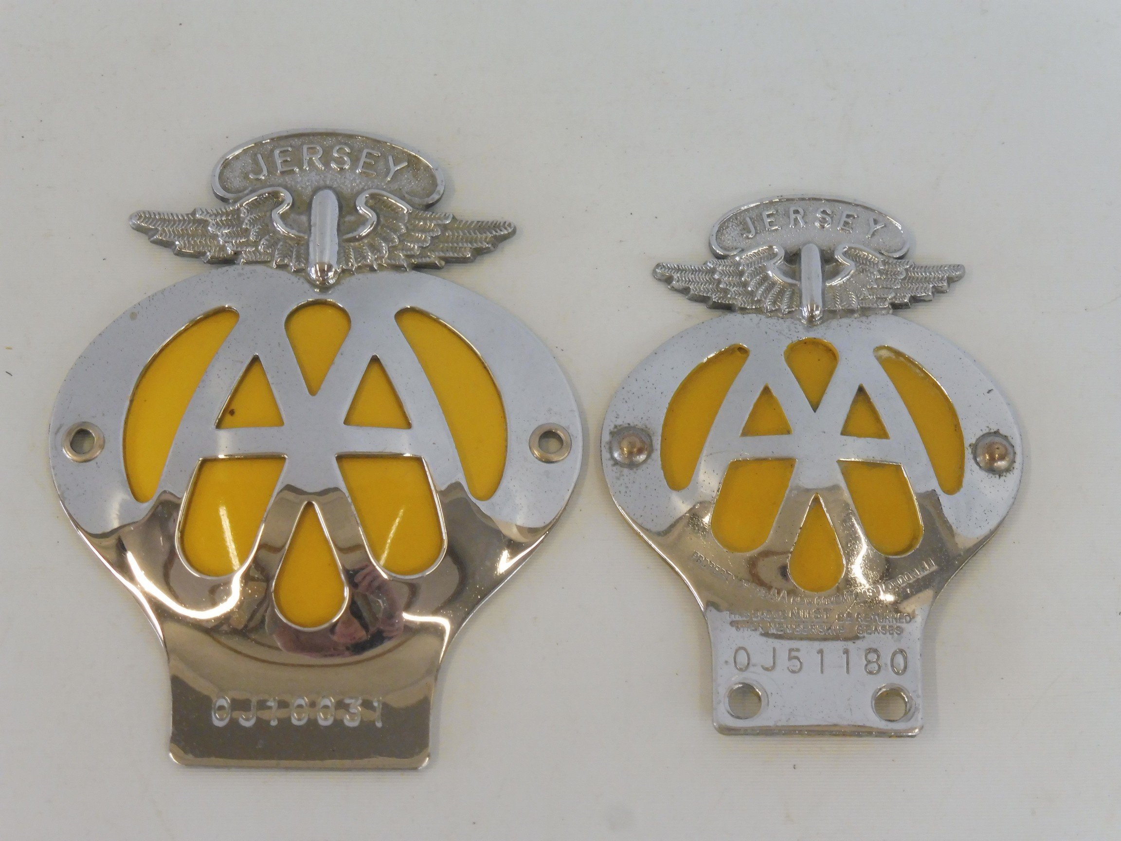 A large AA Jersey car badge, no OJ10031 and one smaller for motorcycles OJJ1180.