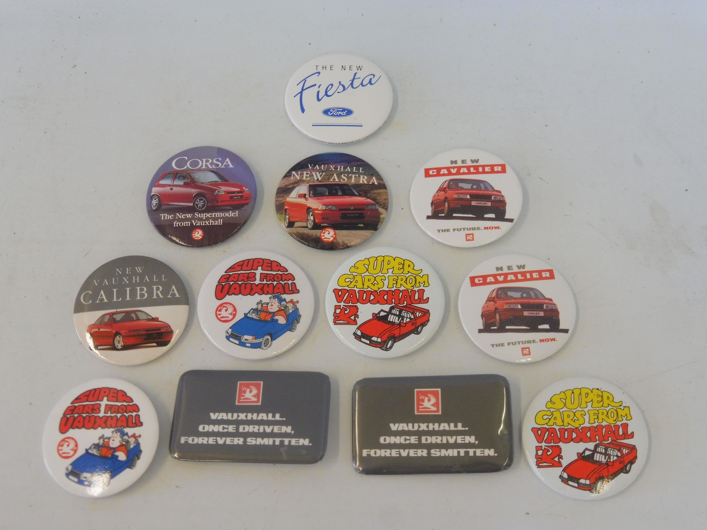 A collection of motoring related promotional badges for Ford and Vauxhall motor cars.