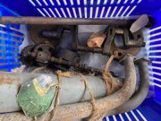 A box of Austin 7 parts comprising crankshaft, half shaft, exhaust system etc.