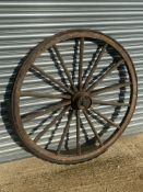 A large wooden and metal rimmed cart wheel with traces of original paint.