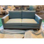 Light blue upholstered two seater sofa
