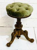 Green velvet upholstered circular stool with adjustable height.