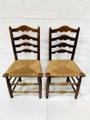 Two oak framed ladder back chairs with string seats.