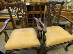 Pair of carved mahogany open arm chairs