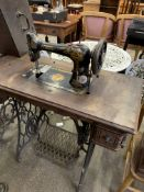Singer vibrating shuttle treadle sewing machine on wooden table . This item carries VAT.