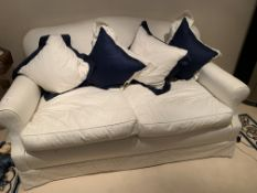 Cream upholstered two seat sofa with seat cushions and four scatter cushions.