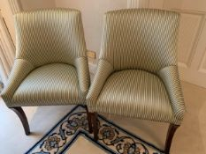 Two upholstered chairs in striped fabric, with sabre legs