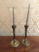 Pair of gilt metal candlesticks with glass storm shades