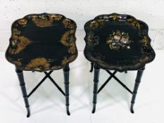 Two black lacquered trays on black painted 4-legged stands,