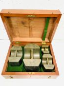 A boxed set of Avoir brass standard weights: 50lbs, 20lbs, 10lbs and 5lbs by De Grave, London.