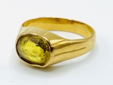 A 22k gold ring set with a yellow sapphire