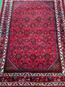 Dark red ground hand knotted wool rug
