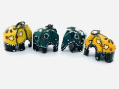 Four carved wooden elephants together with four metal rings.