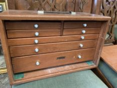 Teak case by Union containing four over three drawers which contains contents
