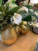 Two gold coloured pots with artificial lilies and roses