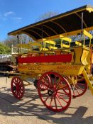 CHARABANC painted yellow and red with 21 wooden seats accessible via a rear staircase