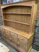Pine dresser with two shelves above four frieze drawers over four cupboards