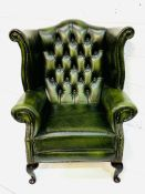 A bottle green leather button back wing back armchair