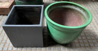 A green ceramic planter and another planter
